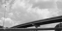 Arching overpasses on an interstate accentuate a vast, textured sky above.