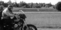 A motorcyclist bows into the headwind as he accelerates on the interstate.